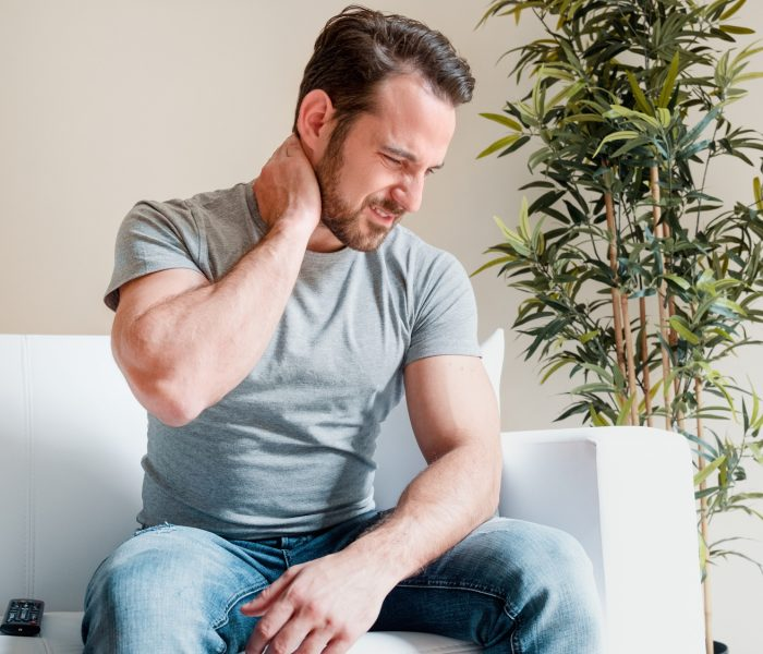 One man suffering neck pain seated on the sofa at home